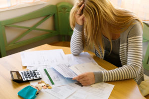 stressed woman agonizing over bills